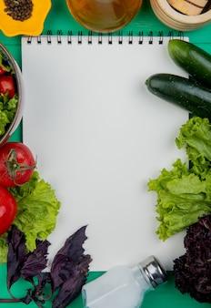Draufsicht auf gemüse als basilikum-tomaten-salat-gurke mit salz und schwarzem pfeffer mit notizblock auf grüner oberfläche mit kopierraum