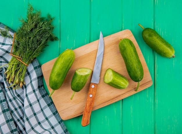 Draufsicht auf gemüse als geschnittene und ganze gurke mit messer auf schneidebrett und dillbündel auf kariertem stoff und grüner oberfläche