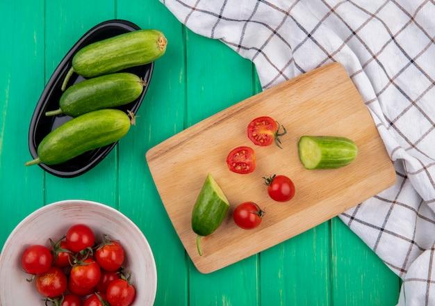 Draufsicht auf gemüse als geschnittene und ganze tomaten und geschnittene gurke auf schneidebrett und ganze auf grüner oberfläche