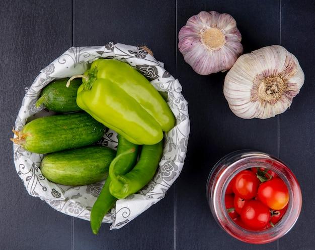 Draufsicht auf gemüse als gurken im korb und tomaten im glas mit knoblauchknollen auf schwarzer oberfläche