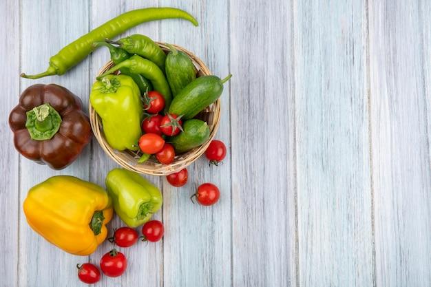 Draufsicht auf gemüse als pfeffer und gurke im korb mit tomatenpaprika herum auf holzoberfläche