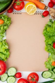 Draufsicht auf gemüse als salat, gurke, karotte und andere mit zitrone und kopierraum