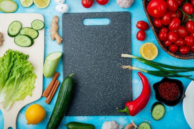 Draufsicht auf gemüse als salat, gurke, zimt ingwer und andere mit schneidebrett auf blauem baxkground