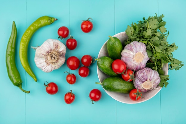 Draufsicht auf gemüse als tomatengurkenkoriander und knoblauch in schüssel mit paprika auf blauer oberfläche