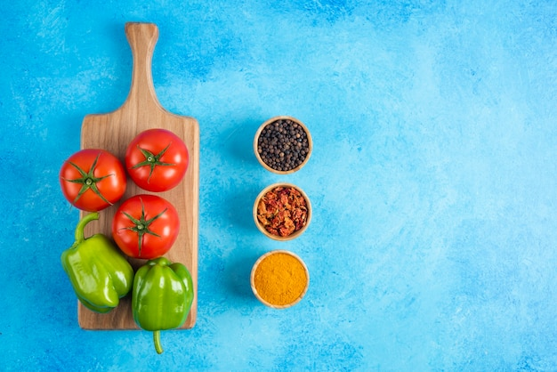 Draufsicht auf gemüse auf holzbrett und gewürzen über blauem tisch.
