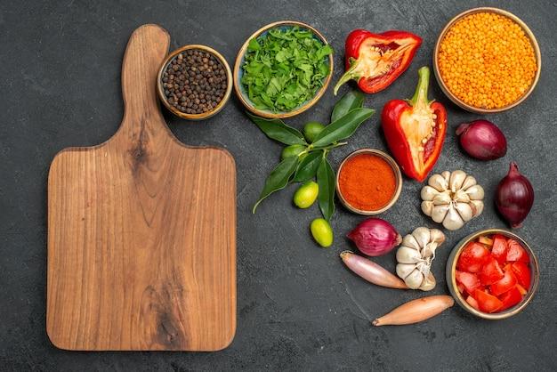 Draufsicht auf gemüse kräuter linsengemüse gewürze zitrusfrüchte das schneidebrett