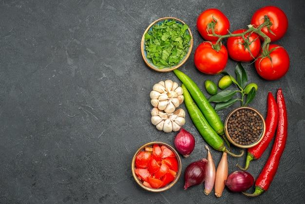 Draufsicht auf gemüse peperoni zwiebel knoblauch tomaten mit stielen kräuter gewürze