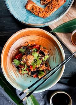 Draufsicht auf gemüsesalat mit gebratenen auberginen, tomaten, kräutern und sesam in einer schüssel, die mit sojasauce auf holz serviert wird