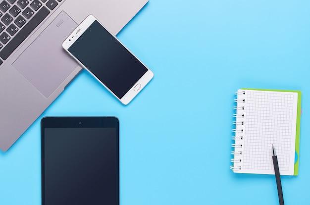 Draufsicht auf geräte auf blauem hintergrund, die zusammensetzung eines laptops, weißer kopfhörer, telefon, glas mit einem getränk und autoschlüssel