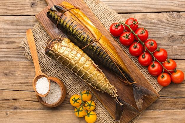 Draufsicht auf geräucherte fische und tomaten