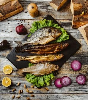 Draufsicht auf geräucherten fisch, der mit salat auf schwarzem servierbrett serviert wird
