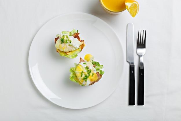 Draufsicht auf geröstete brötchen mit speck, salat und pochiertem ei