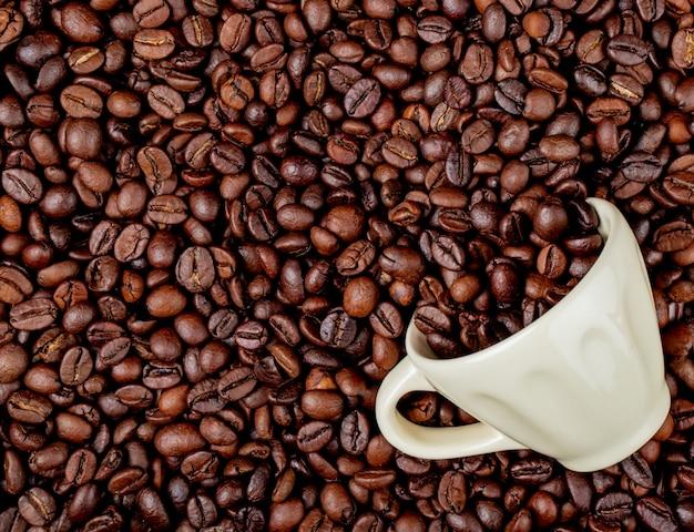 Draufsicht auf geröstete kaffeebohnen, die von einer keramikschale auf kaffeebohnenhintergrund verstreut werden