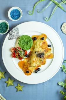 Draufsicht auf geröstete kartoffelscheiben mit avocadosauce und kirschtomaten auf einem teller