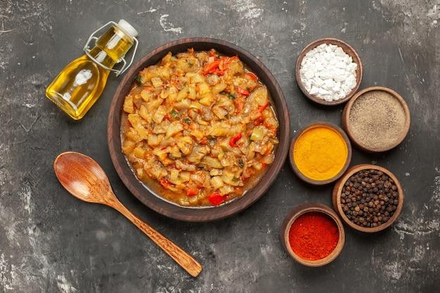Draufsicht auf gerösteten auberginensalat in schüssel, ölflasche, holzlöffel und verschiedenen gewürzen in schalen auf dunkler oberfläche