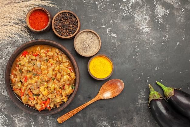 Draufsicht auf gerösteten auberginensalat in schüssel und verschiedene gewürze in kleinen schalen holzlöffel auberginen auf dunkler oberfläche