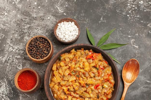 Draufsicht auf gerösteten auberginensalat in schüssel und verschiedene gewürze in schalen holzlöffelblatt auf dunkler oberfläche