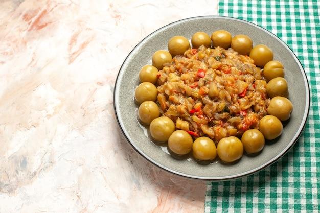 Draufsicht auf gerösteten auberginensalat und eingelegte pflaumen auf teller auf nackter oberfläche Kostenlose Fotos