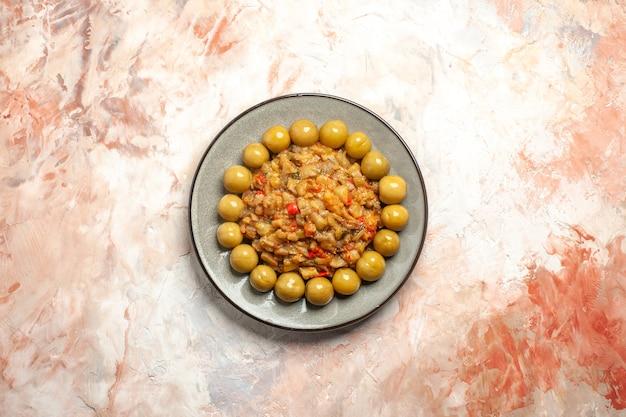 Draufsicht auf gerösteten auberginensalat und eingelegte pflaumen auf teller auf nackter oberfläche