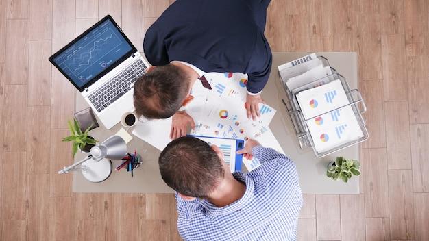 Draufsicht auf geschäftsleute, die an der unternehmensstrategie arbeiten und die managementpapiere analysieren