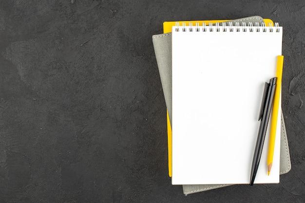 Draufsicht auf geschlossene spiralnotizbücher und kugelschreiber rechts auf schwarz