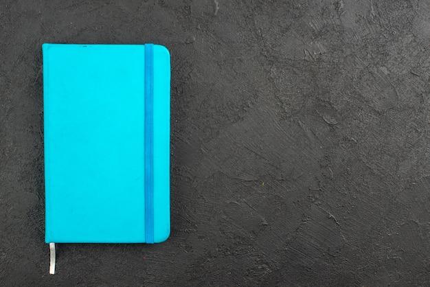 Draufsicht auf geschlossenes blaues notizbuch auf der rechten seite auf schwarz