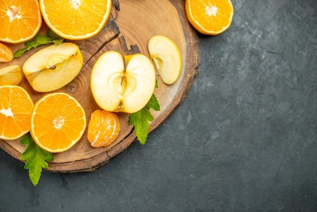Draufsicht auf geschnittene äpfel und orangen auf holzbrett auf dunklem hintergrund
