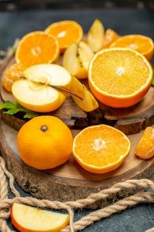 Draufsicht auf geschnittene äpfel und orangen auf holzbrettcocktail auf dunklem hintergrund