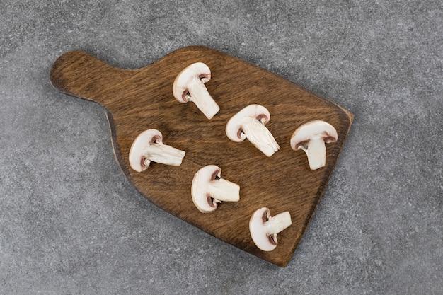 Draufsicht auf geschnittene champignons auf holzbrett