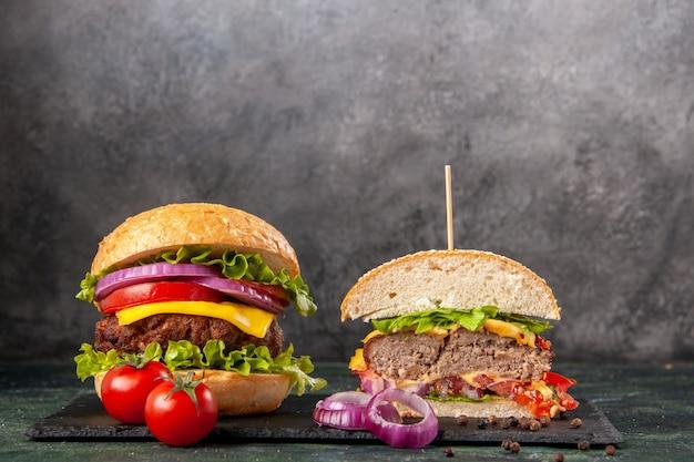Draufsicht auf geschnittene ganze leckere sandwiches und tomaten mit stielzwiebeln auf schwarzem tablett auf dunkler mischfarboberfläche