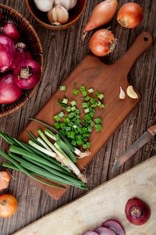 Draufsicht auf geschnittene grüne zwiebel auf schneidebrett mit anderen zwiebeln herum auf hölzernem hintergrund