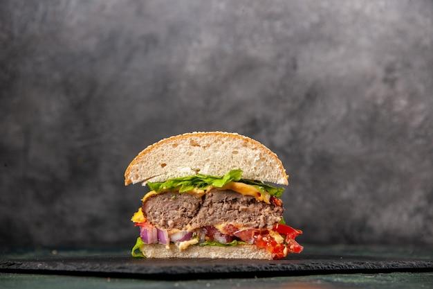 Draufsicht auf geschnittene leckere sandwiches auf schwarzem tablett auf dunkler mischfarboberfläche