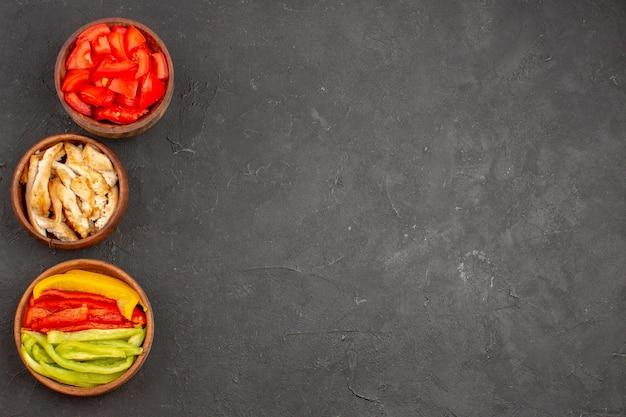 Draufsicht auf geschnittene rote tomaten mit hühnchen und paprika auf schwarz