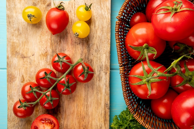 Draufsicht auf geschnittene und ganze tomaten auf schneidebrett mit anderen in korb und koriander auf blau