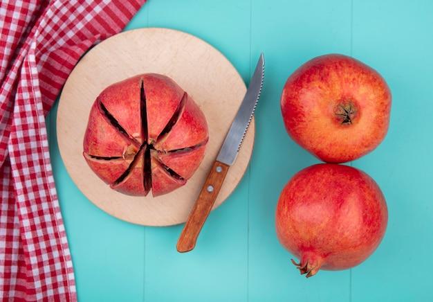 Draufsicht auf geschnittenen granatapfel mit messer auf schneidebrett und ganze mit kariertem stoff auf blau