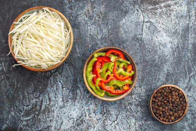 Draufsicht auf geschnittenen kohl mit paprika auf hellgrauer oberfläche