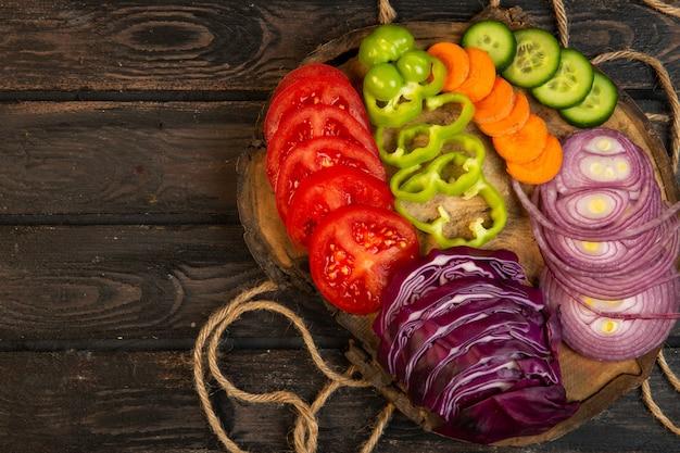 Draufsicht auf geschnittenes gemüse rotkohl zwiebeltomaten paprika karotte und gurken auf einem holzbrett j