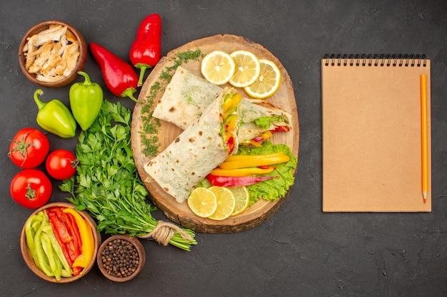 Draufsicht auf geschnittenes shaurma-fleischsandwich mit zitronengrün auf schwarz