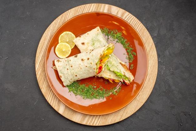 Draufsicht auf geschnittenes shaurma köstliches fleischsandwich in der platte auf schwarz