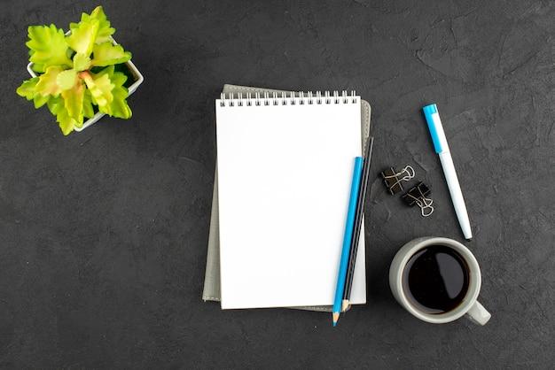 Draufsicht auf gestapelte geschlossene spiralnotizbücher und stifte eine tasse schwarze teeblume in weißem topf auf dunkelheit