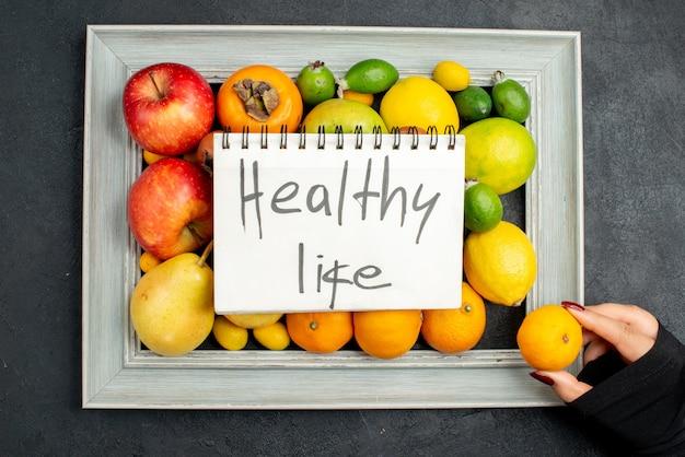 Draufsicht auf gesunde lebensaufschrift auf spiralnotizbuch und hand, die eine mandarine aus der sammlung frischer früchte im bilderrahmen auf dunklem hintergrund nimmt