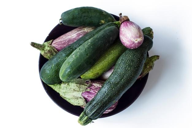 Draufsicht auf gesundes gemüse aus biologischem anbau, einschließlich auberginen, gurken und zucchini. auf einem weißen hintergrund isoliert