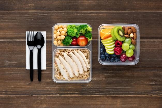 Draufsicht auf gesundes nährstoffreiches essen, das in take-away-kisten mit löffel und gabel auf holztisch gesetzt wird, um zu essen