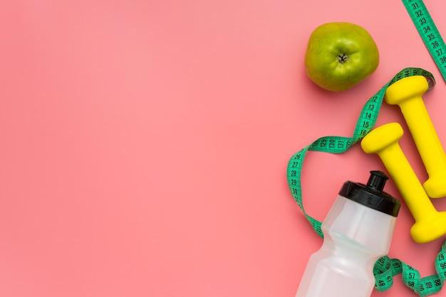 Draufsicht auf gewichte mit maßband und apfel