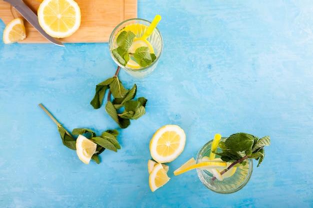 Draufsicht auf gläser mit hausgemachter limonade auf blauem vintage-schreibtisch