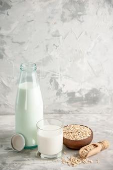 Draufsicht auf glasflasche und tasse gefüllt mit milch auf holztablett und gestapelten kekslöffel haferflocken in braunem topf auf weißem tisch auf eishintergrund