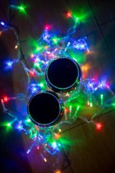 Draufsicht auf glasweingläser in leuchtender weihnachtsgirlande auf dunklem hintergrund
