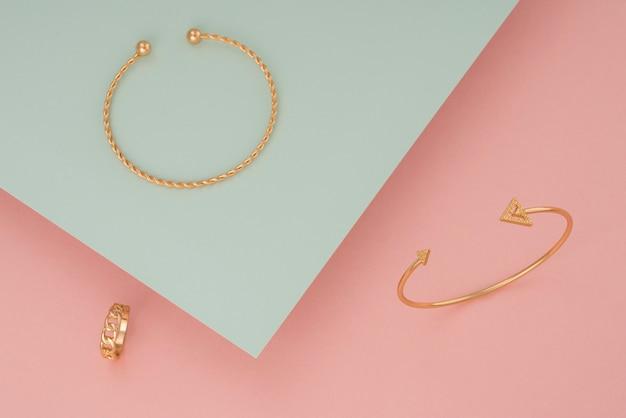 Draufsicht auf goldene armbänder und ring