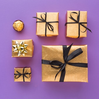 Draufsicht auf goldene geschenke mit süßigkeiten