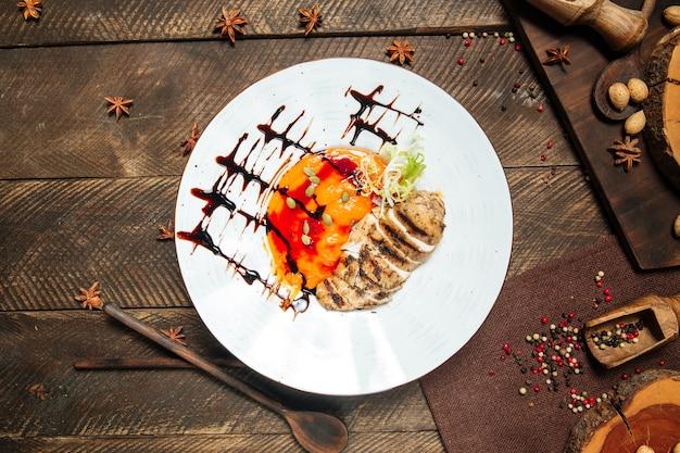 Draufsicht auf gourmet-hühnerbrust mit erbsenbrei-sauce und kürbiskernen